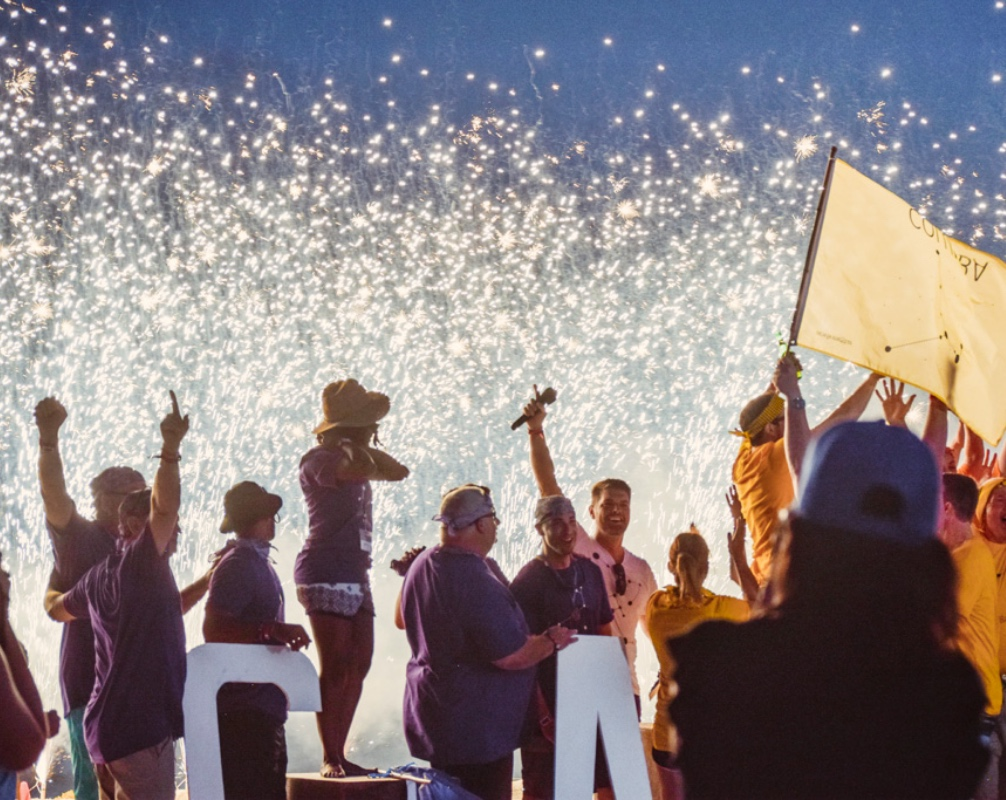 Group of Employees Celebrating with Fireworks in Background at Work Event